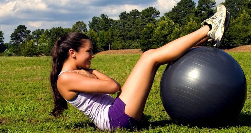 バランスボールでトレーニング中の女性