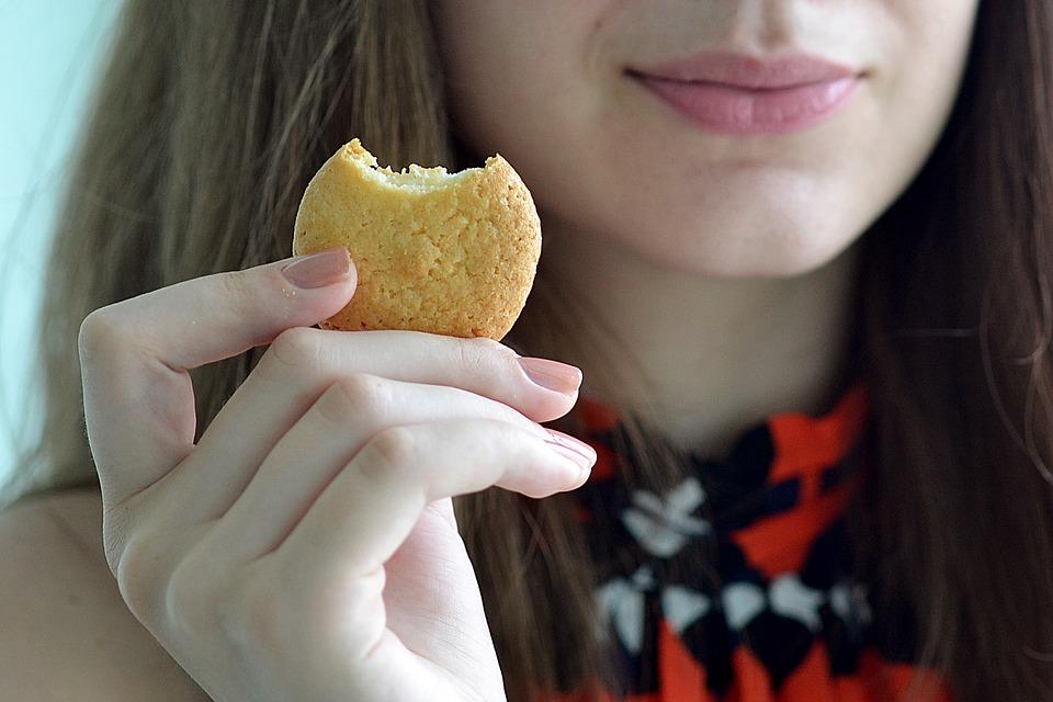 クッキー、クラッカーを持つ女性